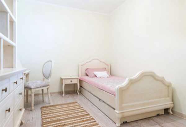 Светлая, простая комната. Кровать с рельефными спинками, простой шкаф, тумбочка, стул и дорожка