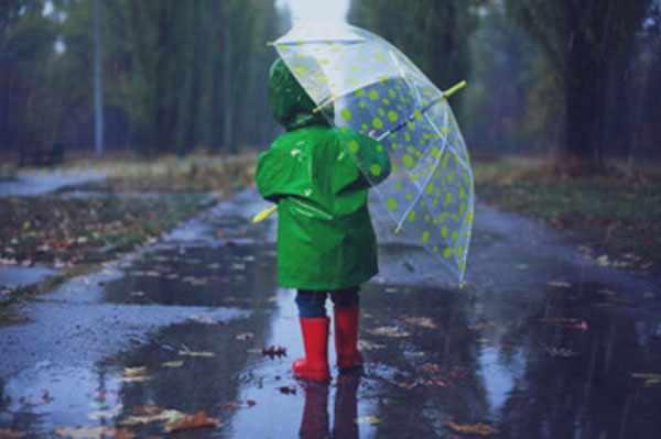 Девочка в плаще и с зонтиком идет по улице. Погода дождливая