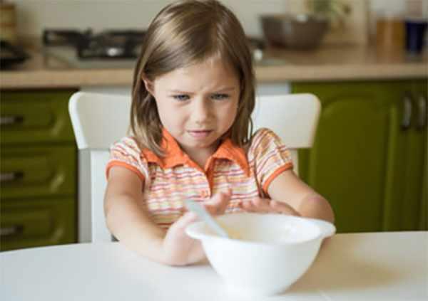 Девочка отодвигает тарелку с едой