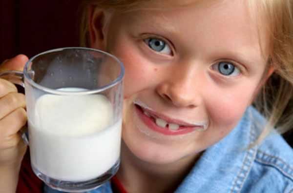 Девочка с молочными усами держит чашку молока