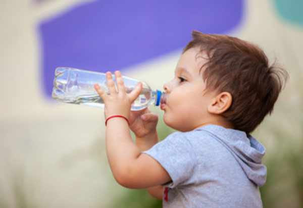 Мальчик пьет воду с бутылочки