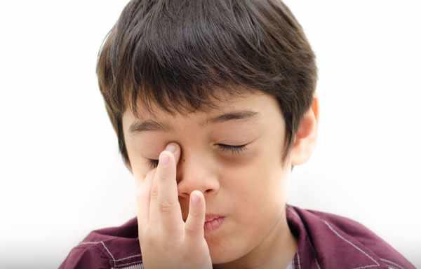 Мальчик с темными мешками под глазами. Трогает пальчиками один глаз