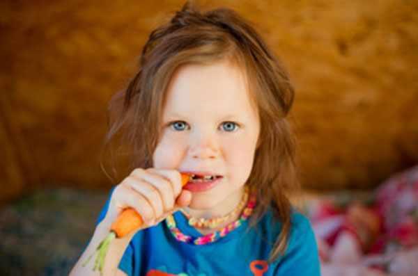 Девочка грызет морковку