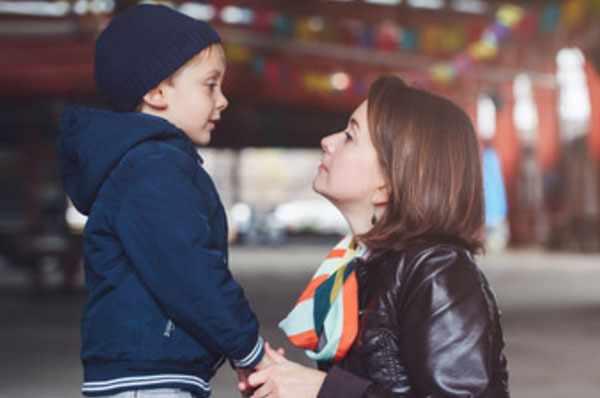 Мама присела на присядки рядом с сыном, пытается что-то ему говорить