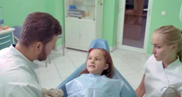 Девочка лежит на стоматологическом кресле. Рядом врач и медсестра
