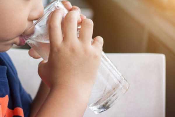 Мальчик пьет воду из стакана