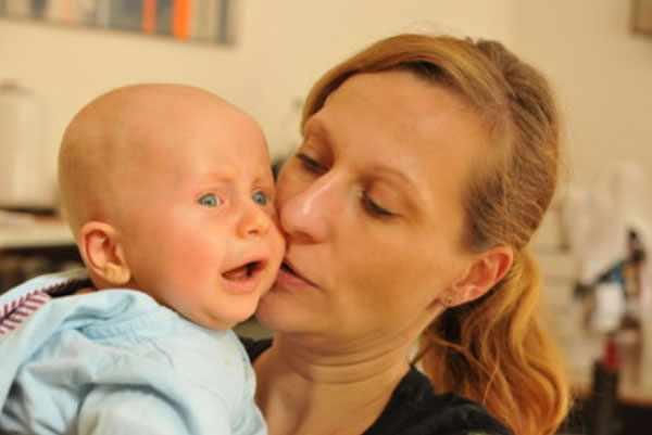 Ребенок без волос плачет у мамы на руках