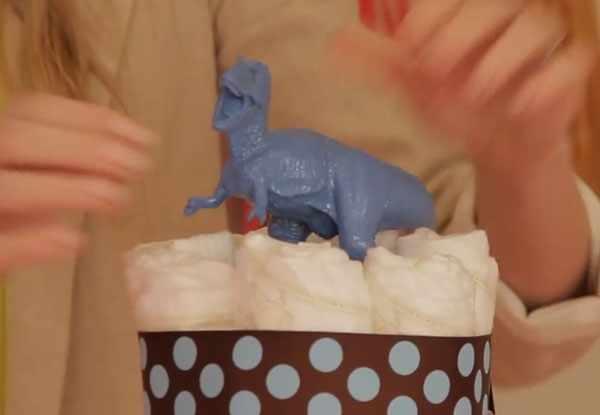 Верхушка торта с черной лентой в голубой горошек. Сверху сидит синий динозавр