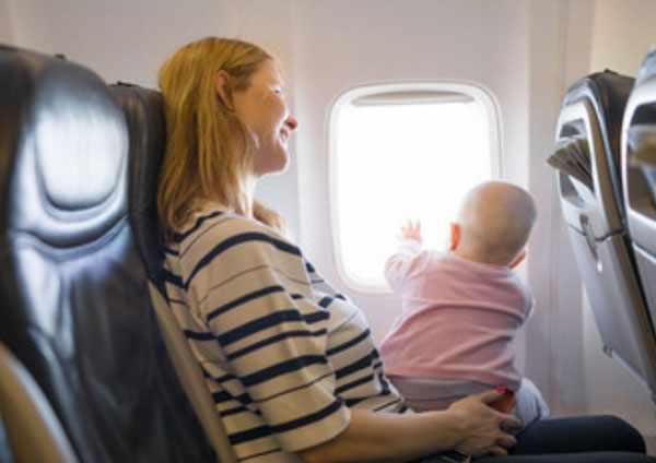 Грудной ребенок сидит у мамы на коленях и смотрит в окно самолета