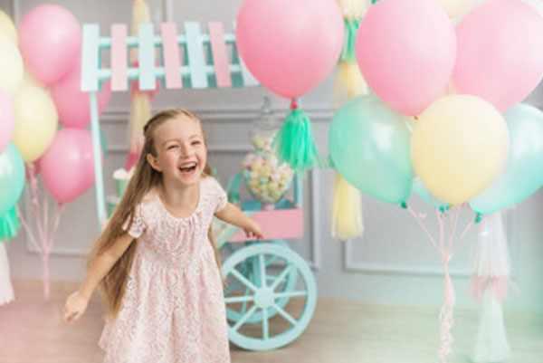 Счастливая девочка. В ее комнате много надутых шаров и тележка со сладостями