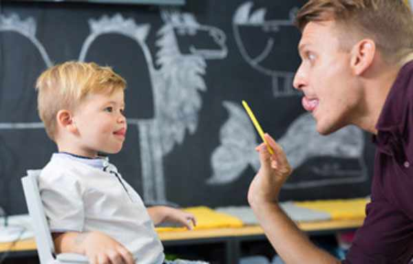 Ребенок выполняет упражнение с логопедом. тянется языком до носика