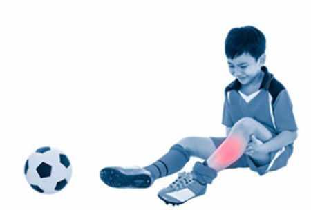Мальчик возле футбольного мяча, голень подсвечена красным цветом (место травмы)