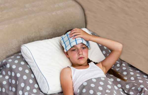 Ребенок лежит в постели. На лбу полотенце, смоченное в воде