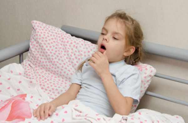 Девочка сидит в постели и кашляет