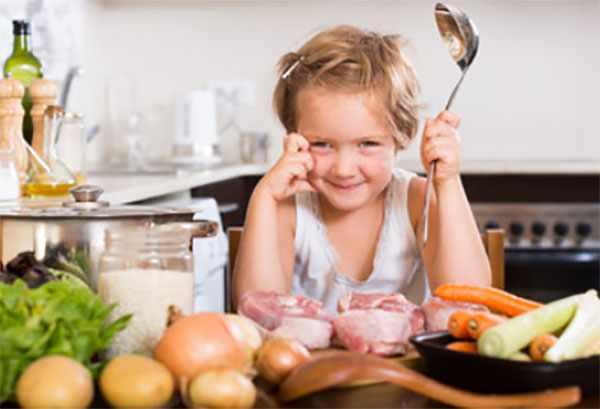 Ребенок с половником в руках, на столе мясо и овощи
