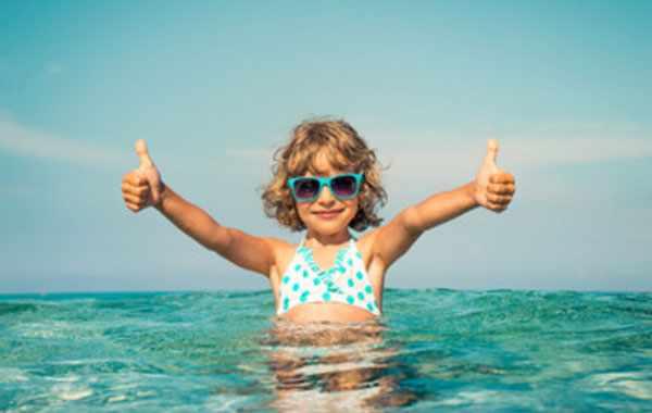 счастливая девочка в солнцезащитных очках на море. стоит в воде