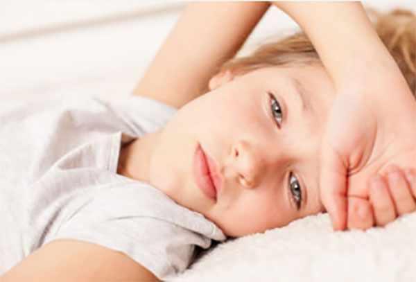 Ребенок с головокружением лежит в постели