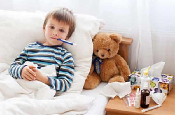 Больной мальчик в постели с градусником во рту