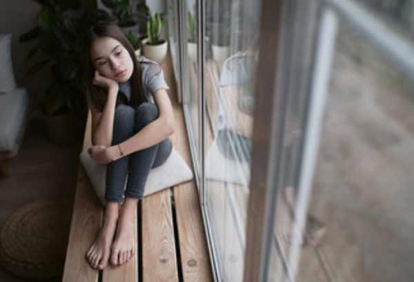 Грустная девочка сидит у окна