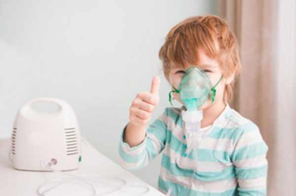 Мальчик с маской для ингаляций на лице показывает пальцем класс