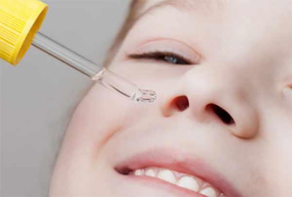 Мальчику закапывают капли в нос