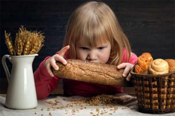 Девочка жадно смотрит на пшеничный хлеб, рядом булочки в корзинке и колосья пшеницы