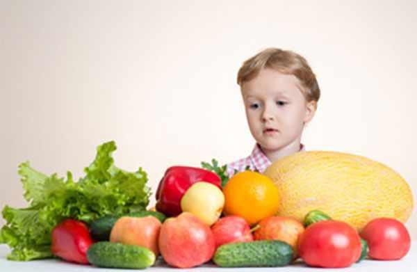 Перед мальчиком на столе лежат овощи и фрукты