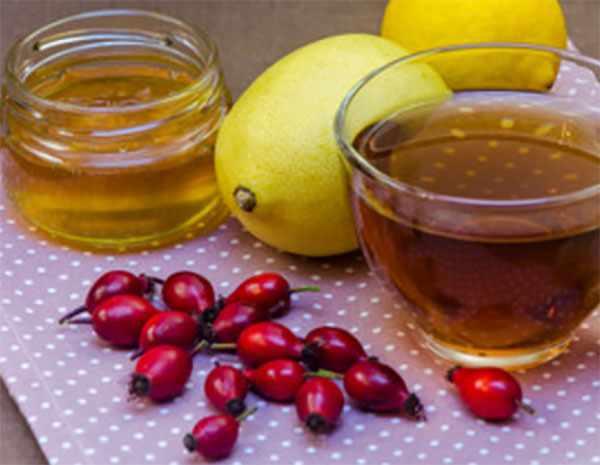 Напиток в стакане, рядом лежит мед, лимон и шиповник