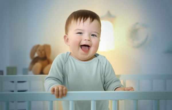 Малыш стоит в кроватке и смеется. В комнате включен ночник