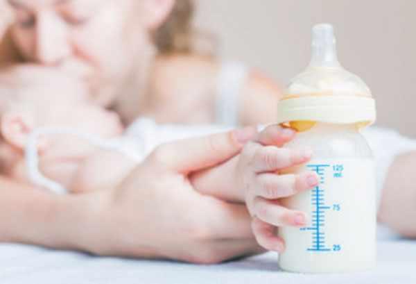 На переднем плане ручка грудничка с бутылочкой с молоком и смесью. На заднем мама, целующая карапуза в лобик