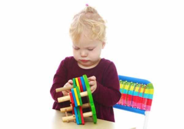 Маленькая девочка занимается с пособием Монтессори