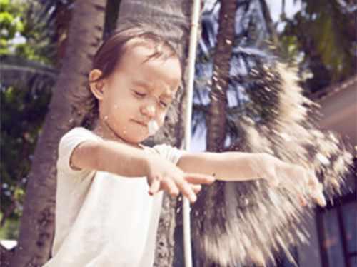 Девочка бросается песком