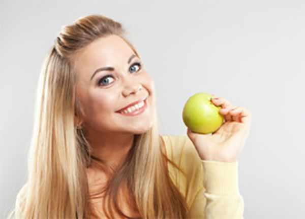Женщина с желто - зеленым яблоком в руке