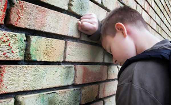 Мальчик с закрытыми глазами облокотился на стену