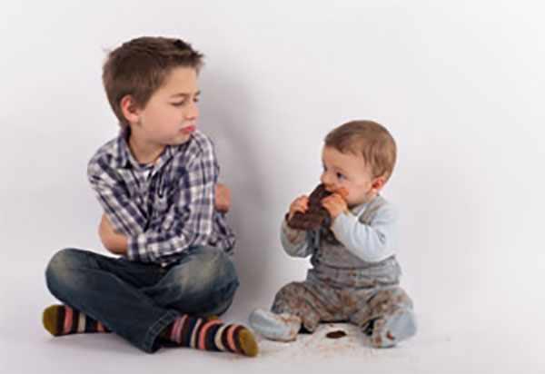 Маленький ребенок весь испачкан в шоколаде. Рядом сидит старший мальчик, который выглядит обиженным