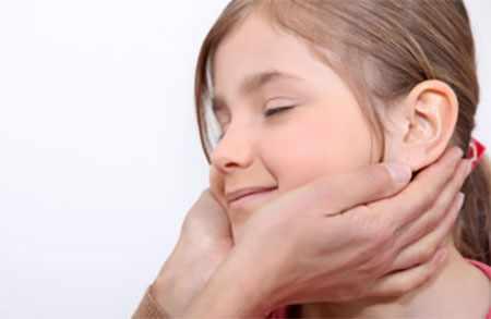 Девочке делают массаж. Руки специалиста опускаются к шее ребенка