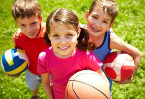 Два мальчика и девочка стоят с мячами в руках