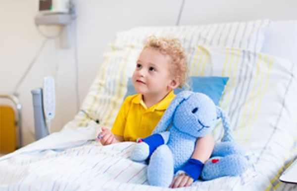 Ребенок сидит на кровати в больничной палате