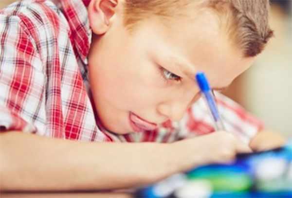 Ребенок что-то задумчиво пишет
