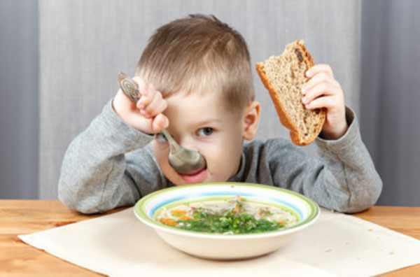 Мальчик ест суп с хлебом