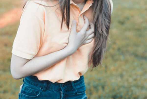 Девочка-подросток держится за сердце, которое болит