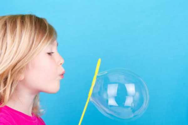 Девочка дует мыльный пузырь