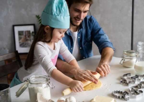 Девочка с папой раскатывают тесто