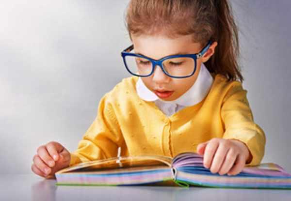 Девочка в очках пытается читать книгу