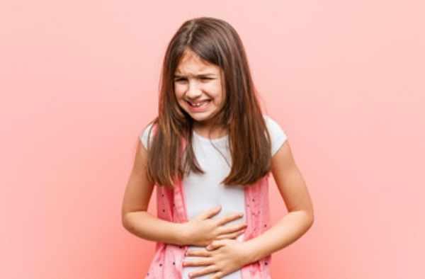 Девочка держится за живот, который болит