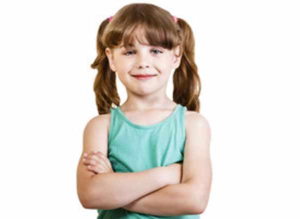Девочка улыбается. Стоит со скрещенными перед собой руками
