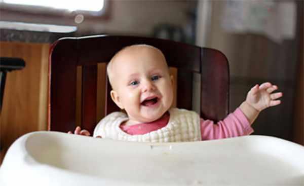 Восьмимесячный ребенок сидит за столиком