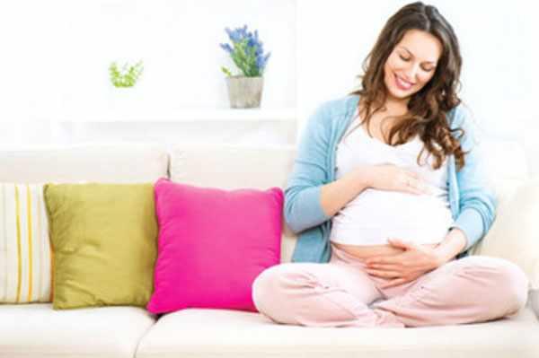 Счастливая беременная женщина сидит на диване и гладит свой живот