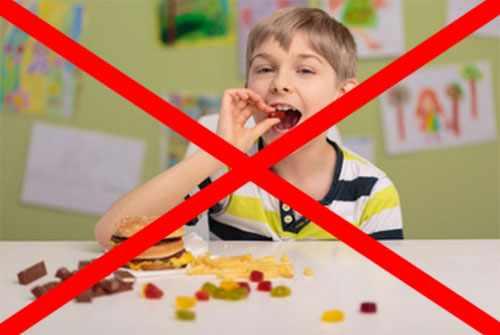 Ребенок ест сладости, перед ним лежат конфеты, в том числе и шоколадные, гамбургер. Фотография перечеркнута