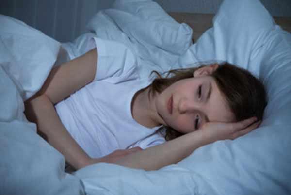Девочка лежит в постели, не может уснуть